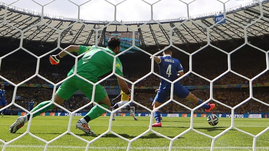 Greece's Kostas Manolas fails to stop the ball as Colombia's Pablo Armero scores the opening goal during the group C World Cup soccer match between Colombia and Greece at the Mineirao Stadium in Belo Horizonte, Brazil, Saturday, June 14, 2014.  (AP Photo/Frank Augstein)