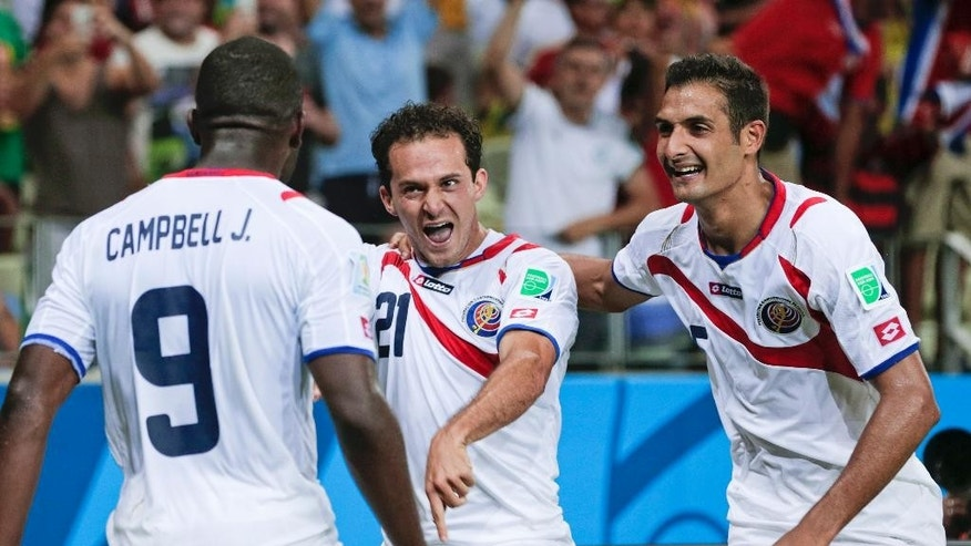 Costa Rica's Marco Urena (21) celebrates with Celso Borges, right, and Joel Campbell (9) after Urena scored his side's third goal during the group D World Cup soccer match between Uruguay and Costa Rica at the Arena Castelao in Fortaleza, Brazil, Saturday, June 14, 2014.