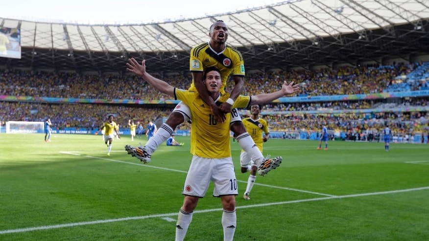 Colombia's James Rodriguez (10) celebrates with his teammate Juan Zuniga after scoring his side's third goal during the group C World Cup soccer match between Colombia and Greece at the Mineirao Stadium in Belo Horizonte, Brazil, Saturday, June 14, 2014. Colombia defeated Greece 3-0. (AP Photo/Fernando Vergara)