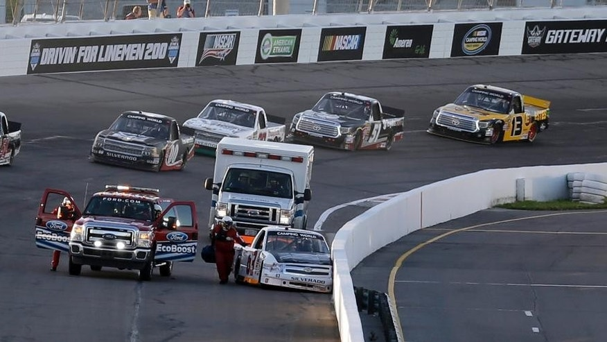 Justin Jennings' car sits against the wall after he crecked during the NASCAR Truck Series auto race at Gateway Motorsports Park on Saturday, June 14, 2014, in Madison, Ill. (AP Photo/Jeff Roberson)
