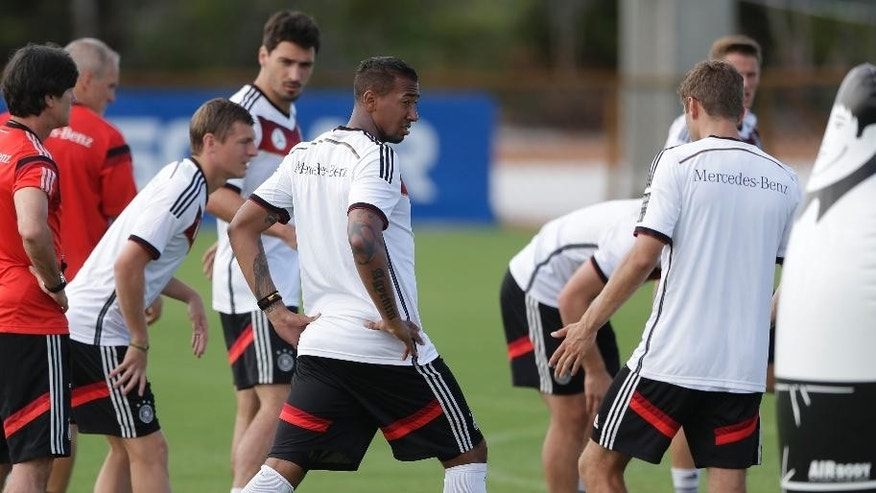 German national soccer player Jerome Boateng, center, talks to Thomas Mueller, right, during a training session in Santo Andre near Porto Seguro, Brazil, Saturday, June 14, 2014. Germany will play in group G of the 2014 soccer World Cup. (AP Photo/Matthias Schrader)