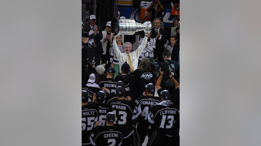 Los Angeles Kings head coach Darryl Sutter raises the Stanley Cup after the Kings beat the New York Rangers in Game 5 of the NHL Stanley Cup Final series Friday, June 13, 2014, in Los Angeles. The Kings won, 3-2. (AP Photo/Mark J. Terrill)