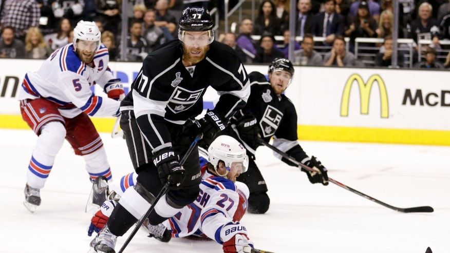 June 14, 2014: Los Angeles Kings center Jeff Carter, left, battles New York Rangers defenseman Ryan McDonagh for the puck during the first overtime period in Game 5 of the NHL Stanley Cup Final.