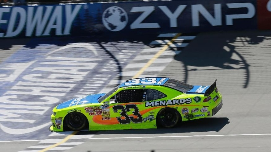 Driver Paul Menard crosses the start/finish line to win the NASCAR Nationwide series auto race at Michigan International Speedway in Brooklyn, Mich., Saturday, June 14, 2014. (AP Photo/Carlos Osorio)