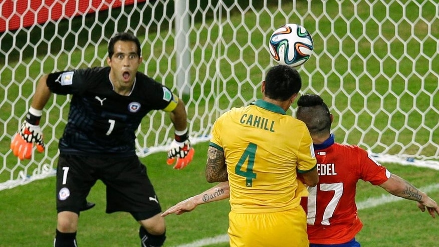 Australia's Tim Cahill, center, scores a header during the group B World Cup soccer match between Chile and Australia in the Arena Pantanal in Cuiaba, Brazil, Friday, June 13, 2014. (AP Photo/Michael Sohn)