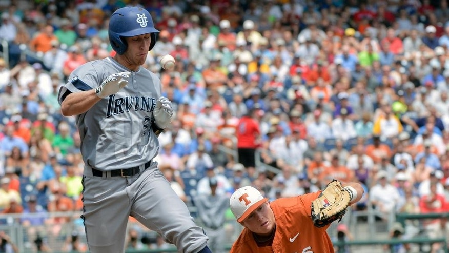 UC Irvine's Taylor Sparks (25) reaches first base on a throwing error by second baseman Brooks Marlow, unseen, as Texas first baseman Kacy Clemens (42) can't catch the ball, in the first inning of an NCAA baseball College World Series game in Omaha, Neb., Saturday, June 14, 2014. (AP Photo/Ted Kirk)