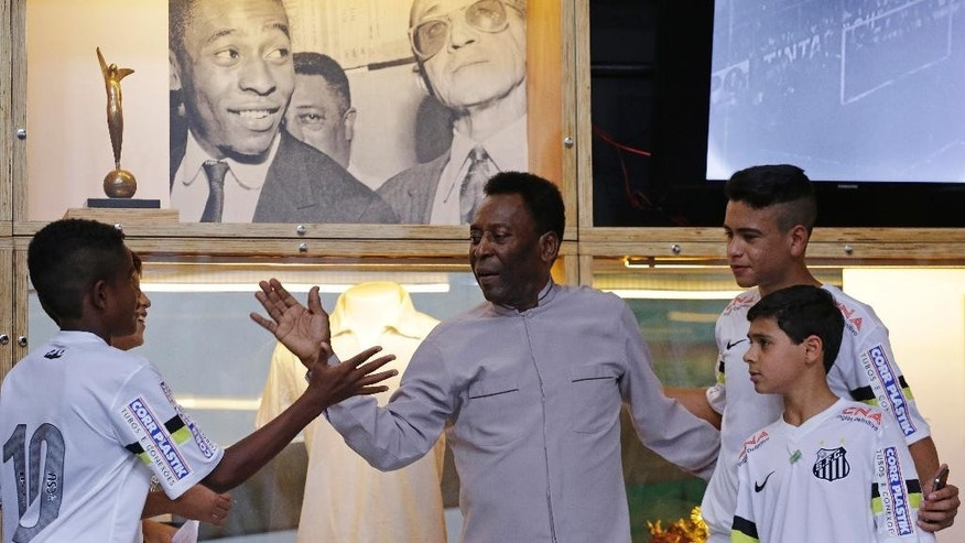 Former great, Pele does a high five with young players of the Santos team during the inauguration of the Pele Museum in Santos, Brazil, Sunday, June 15, 2014. The Pele Museum exhibits his personal collection, pictures, films, trophies and printed material about his history as a soccer player and personality. (AP Photo/Nelson Antoine)