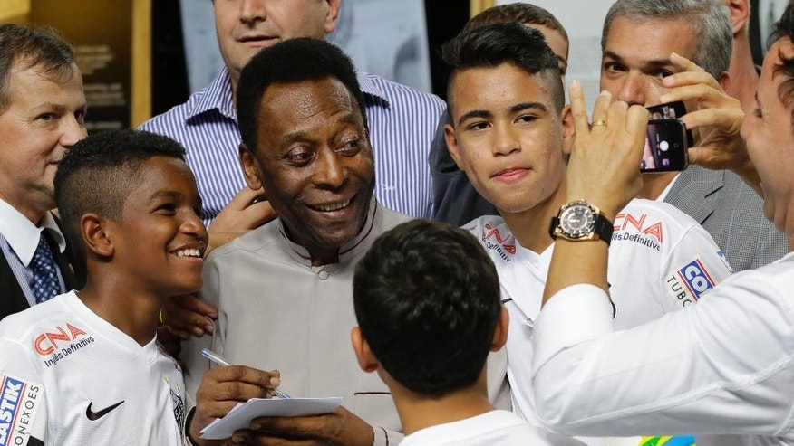 Soccer great, Pele pose for a photo next to young players of the Santos soccer team during the inauguration of the Pele Museum in Santos, Brazil, Sunday, June 15, 2014. The Pele Museum exhibits his personal collection, pictures, films, trophies and printed material about his history as a soccer player and personality. (AP Photo/Nelson Antoine)