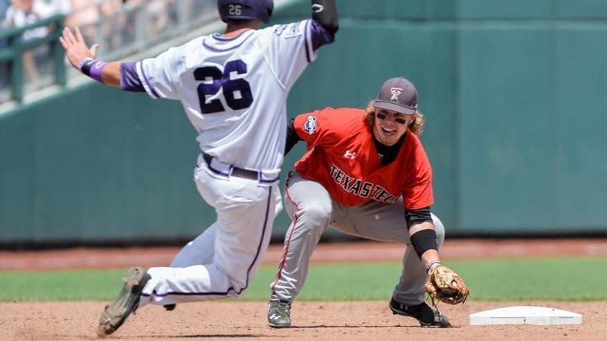 Texas Tech shortstop Tim Proudfoot, right, waits to tag out Keaton Jones (26) who was caught stealing second base in the third inning of an NCAA baseball College World Series game in Omaha, Neb., Sunday, June 15, 2014. (AP Photo/Ted Kirk)