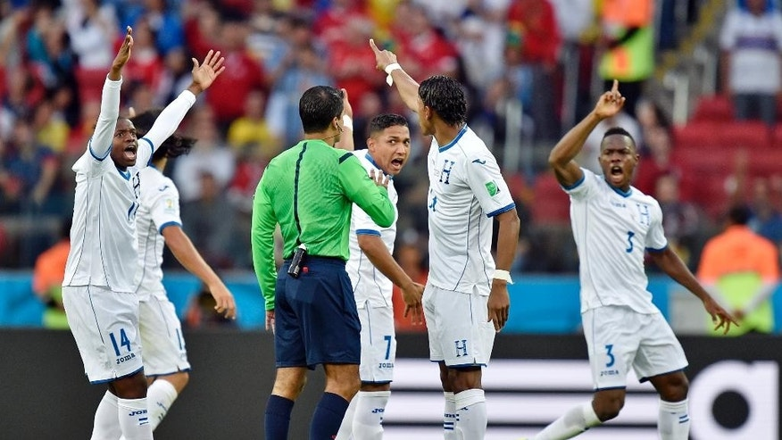 Honduras players argue with referee Sandro Ricci from Brazil after Honduras' goalkeeper Noel Valladares' own goal during the group E World Cup soccer match between France and Honduras at the Estadio Beira-Rio in Porto Alegre, Brazil, Sunday, June 15, 2014. (AP Photo/Martin Meissner)