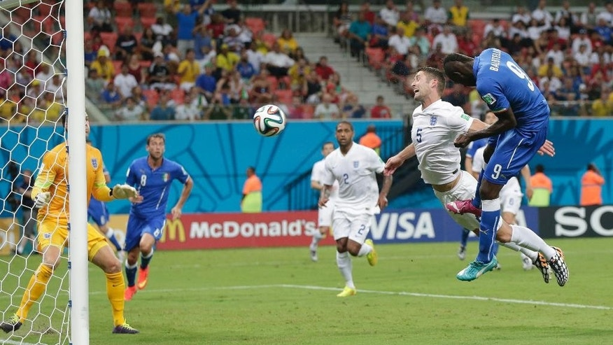 Italy's Mario Balotelli (9) heads the ball past England's Gary Cahill (5) and goalkeeper Joe Hart, left, to score Italy's second goal during the group D World Cup soccer match between England and Italy at the Arena da Amazonia in Manaus, Brazil, Saturday, June 14, 2014. (AP Photo/Marcio Jose Sanchez)
