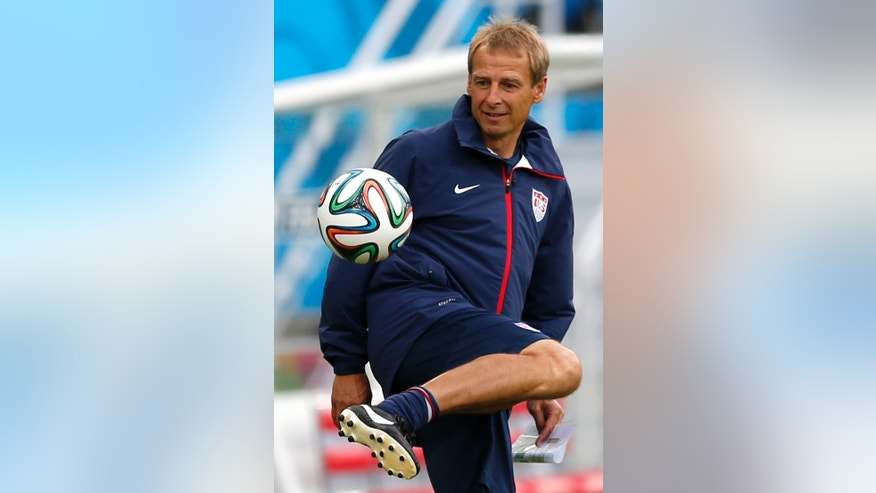 United States' head coach Jurgen Klinsmann juggles a soccer ball before an official training session the day before the group G World Cup soccer match between Ghana and the United States at the Arena das Dunas in Natal, Brazil, Sunday, June 15, 2014.  (AP Photo/Julio Cortez)
