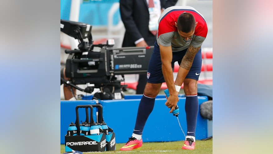 United States' Clint Dempsey uses a Powerade bottle to spray liquid on his soccer boots during an official training session the day before the group G World Cup soccer match between Ghana and the United States at the Arena das Dunas in Natal, Brazil, Sunday, June 15, 2014.  (AP Photo/Julio Cortez)
