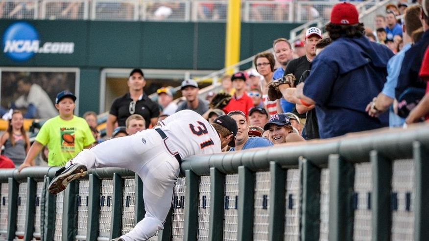 Virginia right fielder Joe McCarthy (31) leans over the barrier as he attempts to catch a foul ball hit by Mississippi's Preston Overbey in the third inning of an NCAA baseball College World Series game in Omaha, Neb., Sunday, June 15, 2014. (AP Photo/Ted Kirk)