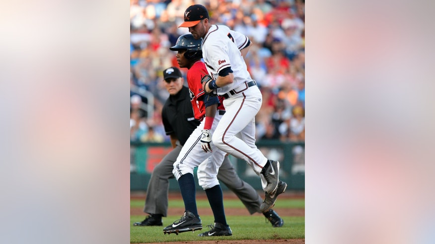 Mississippi's Errol Robinson is tagged out by Virginia second baseman Branden Cogswell, right, after he was caught in a run down between first and second bases, in the third inning of an NCAA baseball College World Series game in Omaha, Neb., Sunday, June 15, 2014. (AP Photo/Ted Kirk)