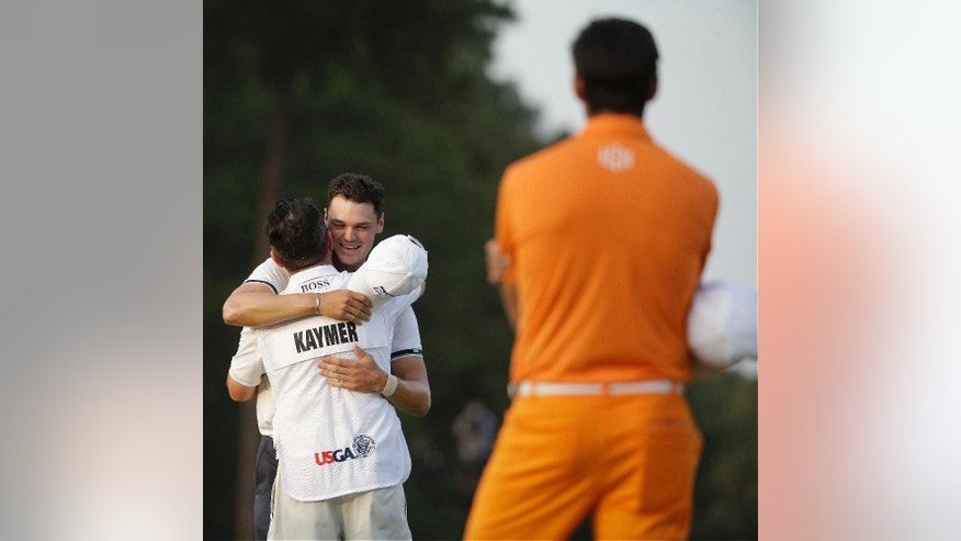 Martin Kaymer, of Germany celebrates with his caddie as Rickie Fowler looks on after winning the U.S. Open golf tournament in Pinehurst, N.C., Sunday, June 15, 2014.  (AP Photo/David Goldman)