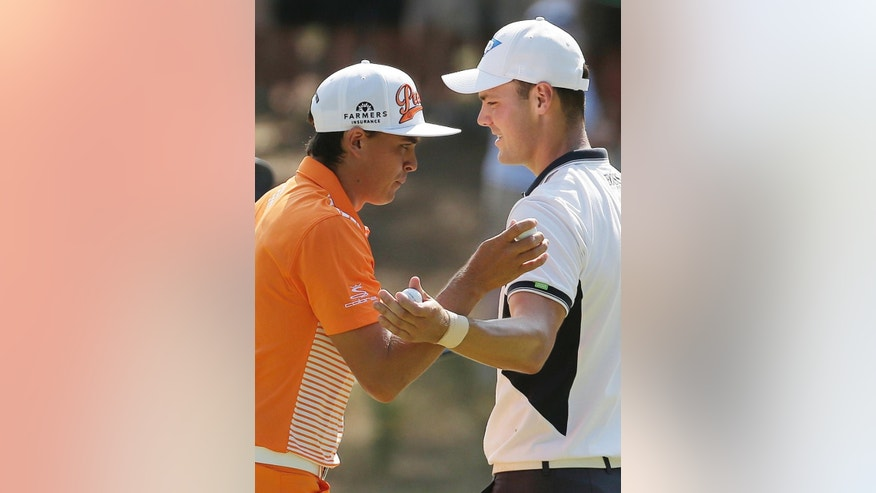 Rickie Fowler, left, and Martin Kaymer, of Germany, walks past each other on the fourth green during the final round of the U.S. Open golf tournament in Pinehurst, N.C., Sunday, June 15, 2014. (AP Photo/Charlie Riedel)