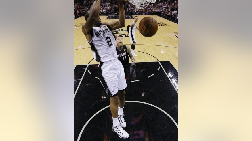 San Antonio Spurs forward Kawhi Leonard (2) dunks against the Miami Heat during the first half in Game 5 of the NBA basketball finals on Sunday, June 15, 2014, in San Antonio. (AP Photo/David J. Phillip, pool)