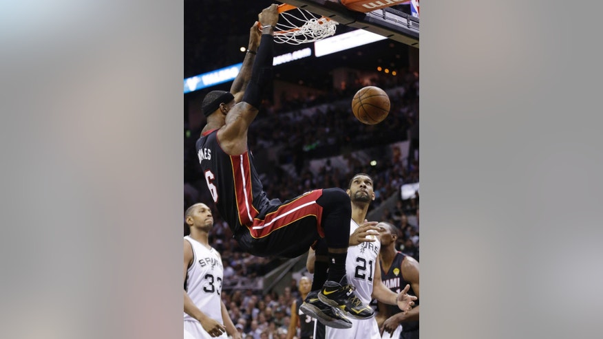 Miami Heat forward LeBron James (6) dunks as San Antonio Spurs forward Boris Diaw (33) and forward Tim Duncan (21) look on during the first half in Game 5 of the NBA basketball finals on Sunday, June 15, 2014, in San Antonio. (AP Photo/David J. Phillip)