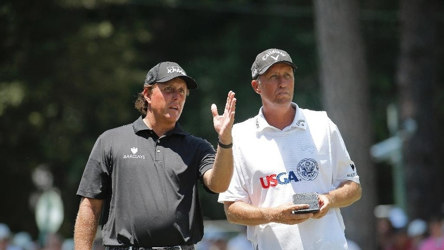 Phil Mickelson talks with his caddy on the third hole during the final round of the U.S. Open golf tournament in Pinehurst, N.C., Sunday, June 15, 2014. (AP Photo/Matt York)
