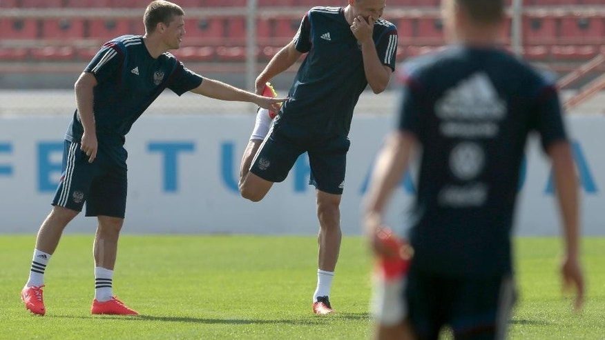 Igor Denisov, left, and Vasily Berezutsky share a joke during the training session of Russian national soccer team in Itu, Brazil, on Sunday, June 15, 2014. Russia will play in group H of the 2014 soccer World Cup. (AP Photo/Ivan Sekretarev)