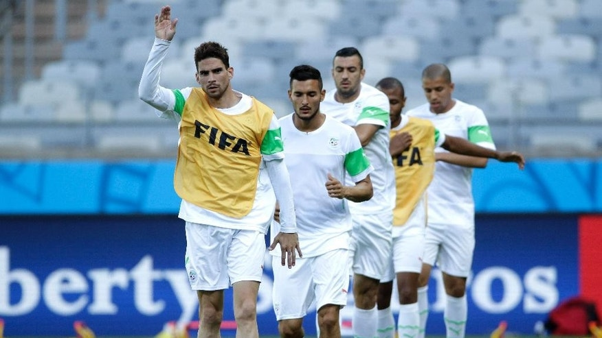 Algeria's Carl Medjani, front, runs with teammates during an official training session the day before the group H World Cup soccer match between Belgium and Algeria, at the Mineirao Stadium in Belo Horizonte, Brazil, Monday, June 16, 2014. (AP Photo/Bruno Magalhaes)