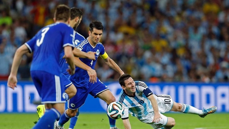 Argentina's Lionel Messi falls to the pitch after being fouled during the group F World Cup soccer match between Argentina and Bosnia at the Maracana Stadium in Rio de Janeiro, Brazil, Sunday, June 15, 2014.    (AP Photo/Victor R. Caivano)