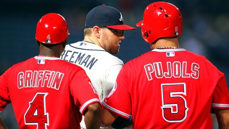 Los Angeles Angels' Albert Pujols (5) talks with Atlanta Braves first baseman Freddie Freeman (5) and first base coach Alfredo Griffin (4) after hitting a single in the third inning inning of a baseball gam,e Sunday, June 15, 2014, in Atlanta. (AP Photo/Todd Kirkland)