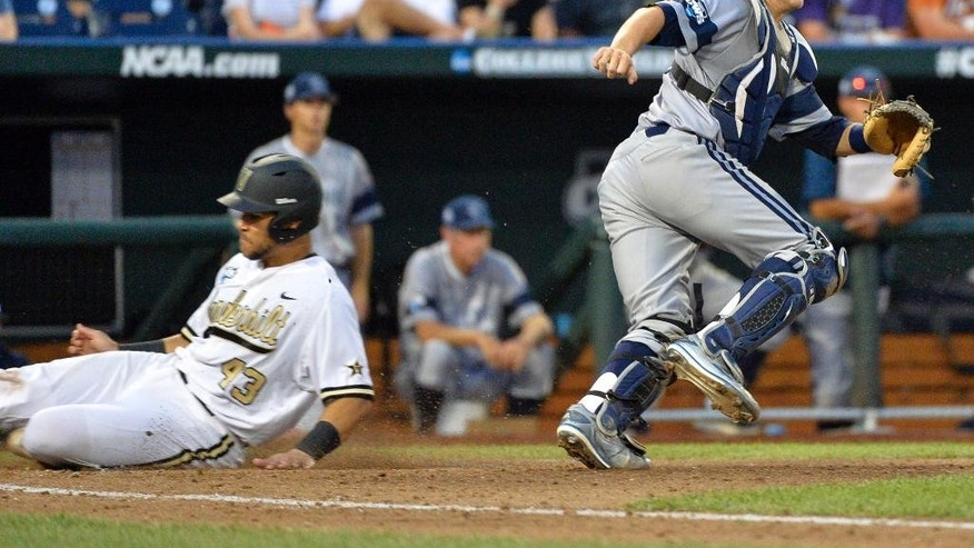 Vanderbilt's Zander Wiel, left, slides home on a sacrifice fly ball by John Norwood, as UC Irvine catcher Jerry McClanahan, right, waits for the ball, in the fifth inning of an NCAA baseball College World Series game in Omaha, Neb., Monday, June 16, 2014. (AP Photo/Ted Kirk)