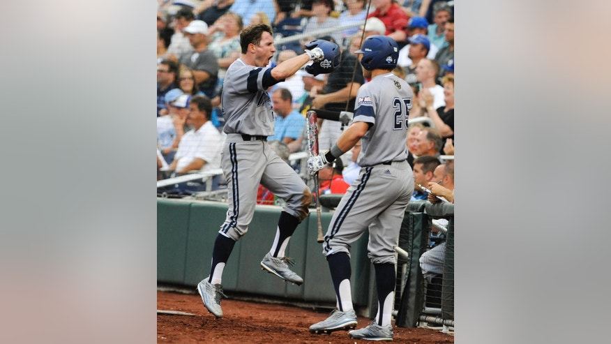 UC Irvine's Grant Palmer, left, celebrates his run against Vanderbilt in the second inning of an NCAA baseball College World Series game in Omaha, Neb., Monday, June 16, 2014. At right is UC Irvine Taylor Sparks (25). (AP Photo/Eric Francis)