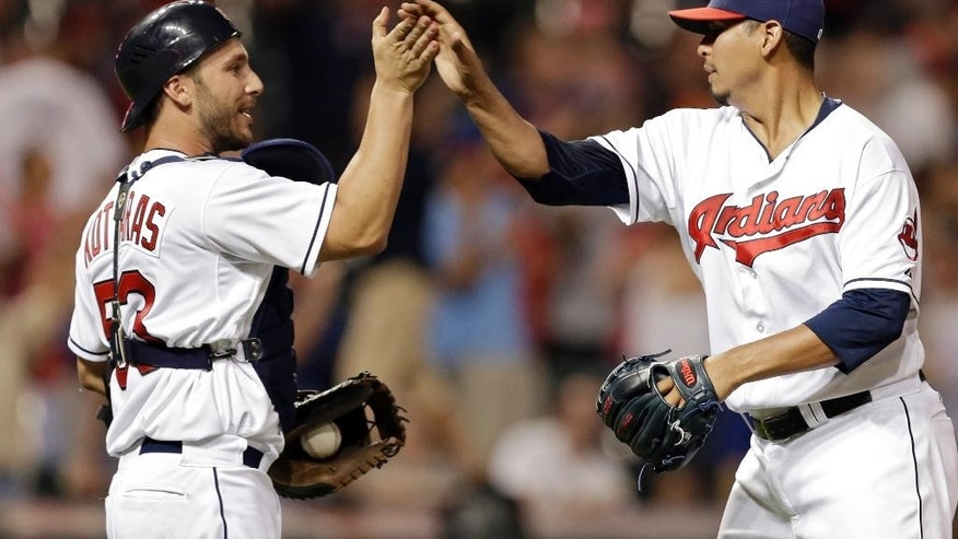 Cleveland Indians catcher George Kottaras, left, congratulates relief pitcher Carlos Carrasco after struck out Los Angeles Angels' Josh Hamilton for the final out in a 4-3 win over the Angels in a baseball game Monday, June 16, 2014, in Cleveland. (AP Photo/Mark Duncan)