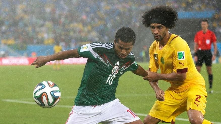 Cameroon's Benoit Assou-Ekotto (2) tries to pull Mexico's Giovani dos Santos (10) away from the ball during the second half of the group A World Cup soccer match between Mexico and Cameroon in the Arena das Dunas in Natal, Brazil, Friday, June 13, 2014.  (AP Photo/Petr David Josek)