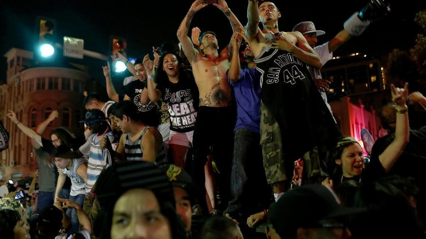 Fans celebrate the Spurs winning the NBA Championship after beating the Miami Heat as they stand on top of a car on Commerce Street in downtown San Antonio on Sunday, June 15, 2014. (AP Photo/San Antonio Express-News, Lisa Krantz)
