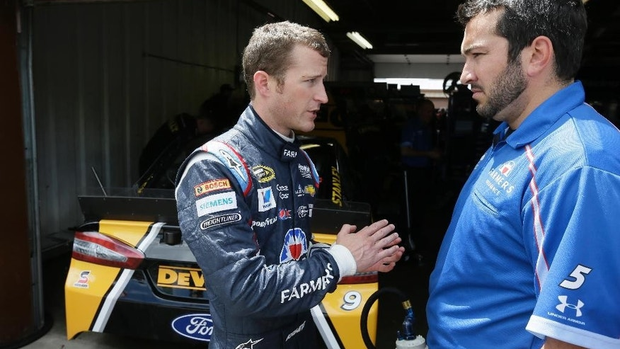 In this photo taken June 13, 2014, driver Kasey Kahne, left,  talks to a crew member in the pit area after a practice session for the NASCAR Sprint Cup series Quicken Loans 400 auto race at Michigan International Speedway in Brooklyn, Mich. Kahne's contract runs through 2015, about the same time Chase Elliott will be ready for a promotion from the driver development program to the big leagues. Hendrick Motorsports has got to put Elliott somewhere, and there's no guarantee Jeff Gordon is going to smile his way into retirement and hand his seat over to Elliott. (AP Photo/Carlos Osorio)