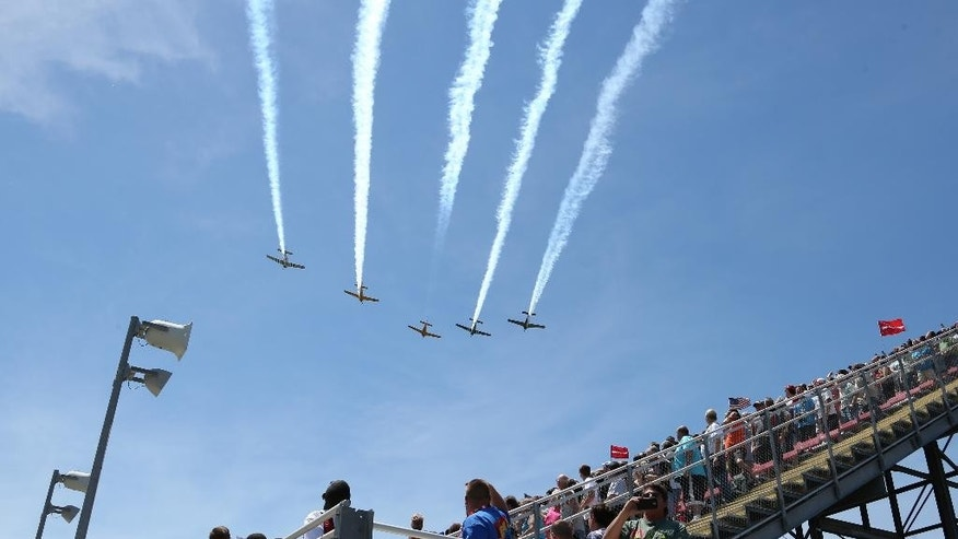 Fans look skyward during a flyover before the NASCAR Quicken Loans 400 auto race at Michigan International Speedway in Brooklyn, Mich., Sunday, June 15, 2014. (AP Photo/Bob Brodbeck)