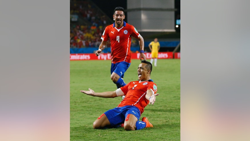 Chile's Mauricio Isla (4) watches as Alexis Sanchez celebrates after scoring his side's first goal during the first half of the group B World Cup soccer match between Chile and Australia in the Arena Pantanal in Cuiaba, Brazil, Friday, June 13, 2014. Sanchez produced a dynamic performance to lead Chile to a 3-1 win over Australia. (AP Photo/Kirsty Wigglesworth)
