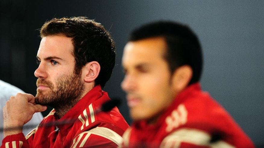 Spain's Pedro Rodriguez, right, and Juan Mata listen, during a press conference at the Atletico Paranaense training center in Curitiba, Brazil, Monday, June 16, 2014. Spain will play Chile in group B World Cup soccer match on Wednesday.  (AP Photo/Manu Fernandez)