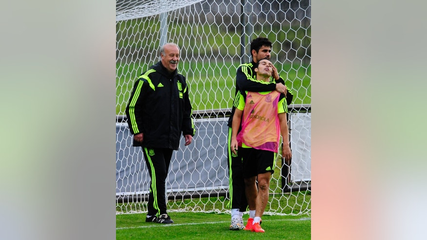 Spain's head coach Vicente del Bosque, left, smiles as Diego Costa, second left, embraces Pedro Rodriguez during a training session at the Atletico Paranaense training center in Curitiba, Brazil, Sunday, June 15, 2014. Spain will play in group B of the Brazil 2014 World Cup. (AP Photo/Manu Fernandez)