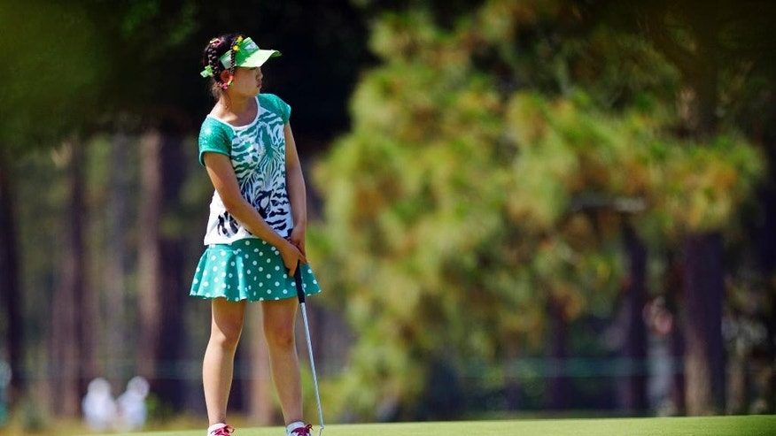 Amateur Lucy Li, 11, putts on the 15th green during a practice round at the U.S. Women's Open golf tournament at Pinehurst No. 2, Tuesday, June 17, 2014, in Pinehurst, N.C. The sixth-grader from California is the youngest qualifier in the history of the U.S. Women's Open.  (AP Photo/The Fayetteville Observer, Abbi O'Leary) MANDATORY CREDIT, MAGS OUT, NO SALES