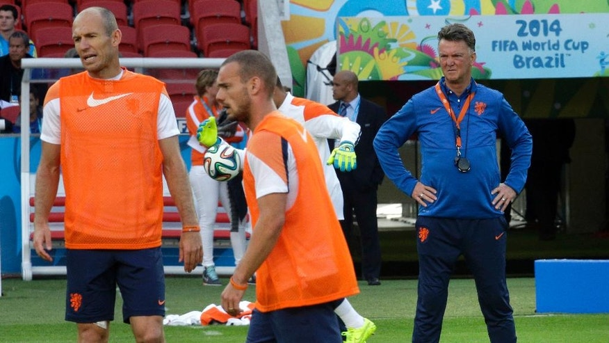 Netherlands' head coach Louis van Gaal, right, looks at the players Arjen Robben, left, and Wesley Sneijder, center, during the official training the day before the group B World Cup soccer match between Australia and the Netherlands at the Estadio Beira-Rio in Porto Alegre, Brazil, Tuesday, June 17, 2014.  (AP Photo/Michael Sohn)