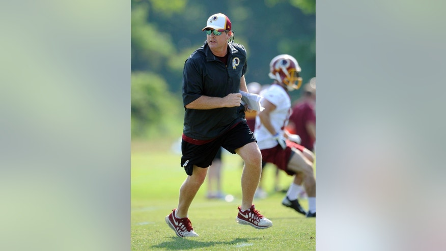 Washington Redskins head coach Jay Gruden runs during NFL football minicamp, Tuesday, June 17, 2014, in Ashburn, Va. (AP Photo/Nick Wass)