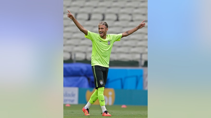 Brazil's Neymar raises his arms during a training session at the Arena Castelao in Fortaleza, Brazil, Monday, June 16, 2014. Brazil plays in group A of the 2014 soccer World Cup. (AP Photo/Andre Penner)