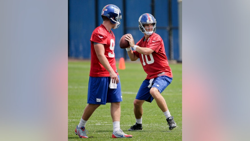 New York Giants quarterback Eli Manning (10) steps back to pass during a drill as quarterback Ryan Nassib (9) looks on during the first day of NFL football minicamp, Tuesday, June 17, 2014, in East Rutherford, N.J. (AP Photo/Julie Jacobson)