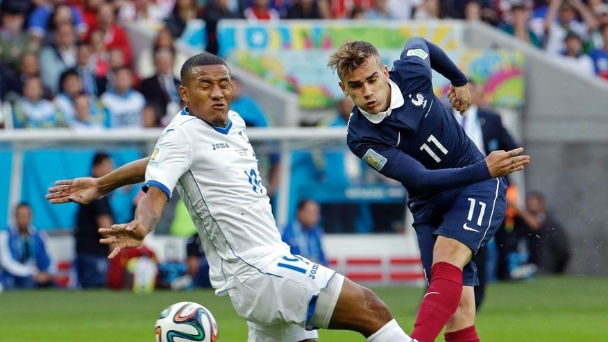 France's Antoine Griezmann drills the ball past Honduras' Luis Garrido during the group E World Cup soccer match between France and Honduras at the Estadio Beira-Rio in Porto Alegre, Brazil, Sunday, June 15, 2014.  (AP Photo/Fernando Vergara)