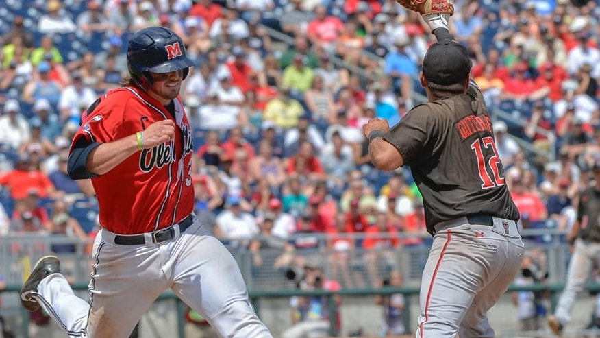 Mississippi's Will Allen, left, is out at first base against Texas Tech first baseman Eric Gutierrez (12) in the fourth inning of an NCAA baseball College World Series elimination game in Omaha, Neb., Tuesday, June 17, 2014. (AP Photo/Ted Kirk)