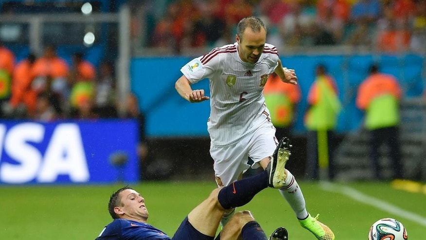 Netherlands' Stefan de Vrij, left, challenges Spain's Andres Iniesta during the group B World Cup soccer match between Spain and the Netherlands at the Arena Ponte Nova in Salvador, Brazil, Friday, June 13, 2014. (AP Photo/Manu Fernandez)