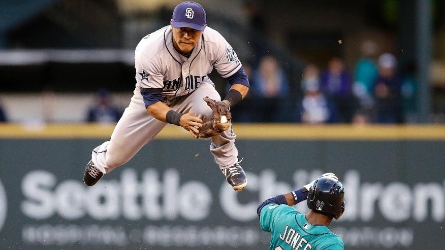 San Diego Padres second baseman Alexi Amarista leaps to get out of the way of sliding Seattle Mariners' James Jones (99) at second base in the fourth inning in a baseball game Monday, June 16, 2014, in Seattle. Jones was forced out, but Robinson Cano was safe at first base on a fielder's choice. (AP Photo/Elaine Thompson)