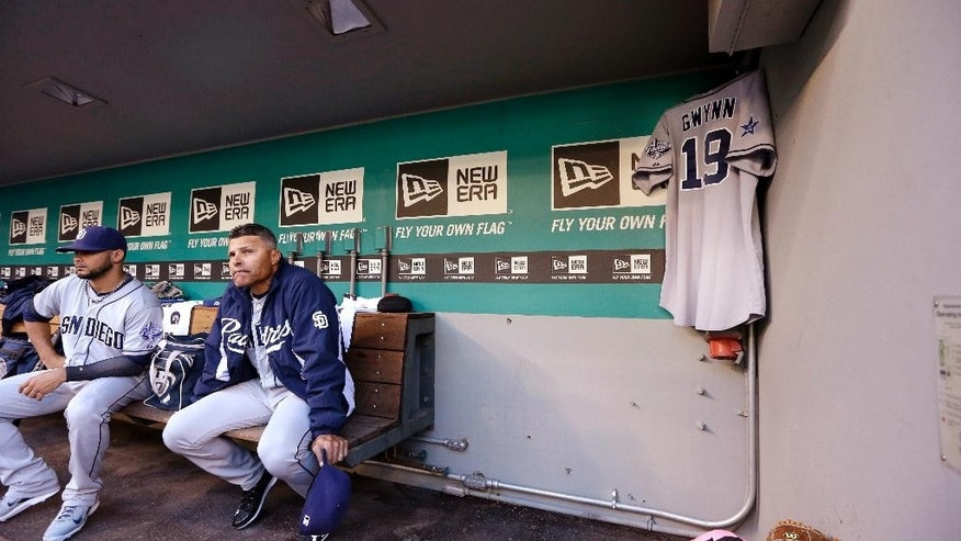 San Diego Padres' Alex Torres, left, and coach Jose Valentine sit near a jersey hanging in the team's dugout honoring Tony Gwynn before a baseball game against the Seattle Mariners Monday, June 16, 2014, in Seattle. It was announced earlier Monday that Gwynn, who had more than 3,100 hits during a career spanning two decades, died at age 54 following a battle with oral cancer. (AP Photo/Elaine Thompson)
