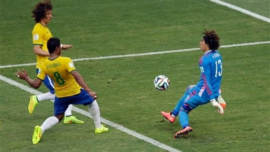 Ochoa deflects a ball as David Luiz and Paulinho approach during the group A World Cup soccer match June 17, 2014.