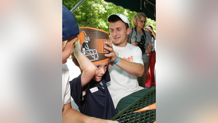 Cleveland Browns quarterback Johnny Manziel jokes around with Thomas Miller, 8, at the Cleveland Metroparks Zoo Tuesday, June 17, 2014, in Cleveland. The Browns rookies interacted with young individuals with Youth Challenge, which assists children with physical disabilities to help them feel comfortable in social settings and get them involved in recreational activities. (AP Photo/Tony Dejak)